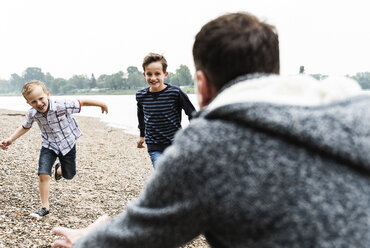 Happy boys running towards father at the riverside - UUF13954