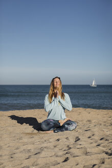 Woman doing yoga on the beach, lotus position - MAUF01430