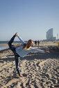 Woman doing yoga on the beach, dancer postition - MAUF01433