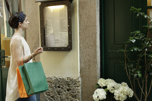 Woman with shopping bags reading menu outside restaurant, Milan, Italy - CUF21239