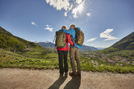 Mature couple standing by roadside, looking at view, rear view, Meran, South Tyrol, Italy - CUF21287