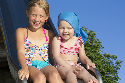 Portrait of girl and female toddler on water slide at Lake Seeoner See, Bavaria, Germany - CUF21308