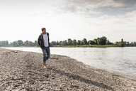 Mature man with red beanie walking at Rhine riverbank - UUF13963