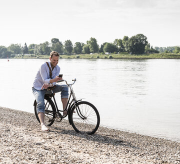 Mature man with bike using smartphone at Rhine riverbank - UUF13978