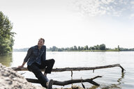 Mature man sitting at Rhine riverbank - UUF13987
