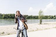 Mature man with bike using smartphone and headphones at Rhine riverbank - UUF14005
