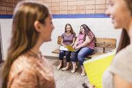 Teenage high school girls talking in corridor - ISF07539