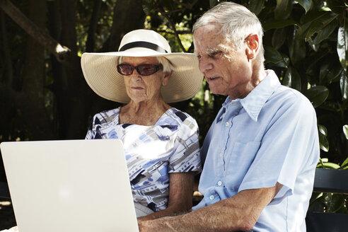 Senior couple sitting using laptop in park - ISF07623