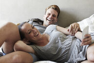 Couple reclining on bed laughing whilst reading smartphone messages - ISF07683