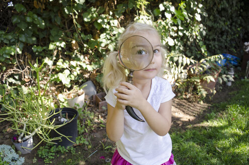 Young girl looking through magnifying glass - ISF07734