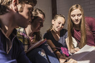 Teenagers reading notes in high school study group - ISF07842