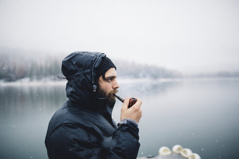 Side view of man smoking pipe by lake, Bass Lake, California, USA - ISF07896