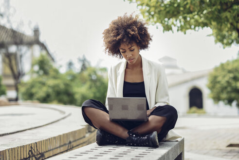Fashionable young woman with curly hair sitting on bench using laptop - JSMF00215