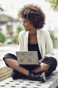 Fashionable young woman with curly hair sitting on bench with laptop laughing - JSMF00218