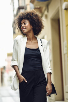 Portrait of fashionable young woman with curly hair in the city - JSMF00224