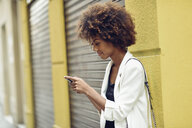 Smiling young woman with curly hair looking at cell phone - JSMF00227