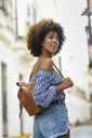 Portrait of fashionable young woman with small leather backpack - JSMF00239