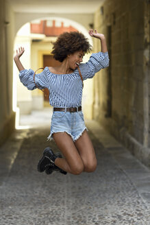 Laughing young woman jumping in the air - JSMF00245