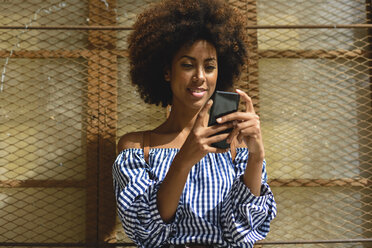 Portrait of fashionable young woman with curly hair looking at smartphone - JSMF00254