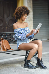 Smiling young woman sitting on bench in the city using tablet - JSMF00257