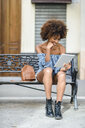 Young woman sitting on bench in the city using tablet - JSMF00260