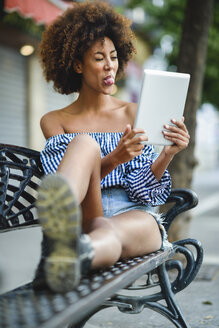 Portrait of young woman sitting on bench with tablet having video chat - JSMF00266