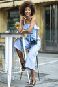 Portrait of fashionable young woman with camera drinking beer outdoors - JSMF00269