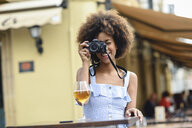 Young woman taking photo with camera outdoors - JSMF00272