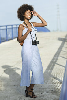 Portrait of fashionable young woman with camera and backpack - JSMF00284