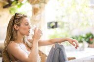 Young woman relaxing on garden patio drinking water - CUF21349