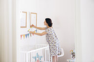Pregnant mid adult woman measuring picture frames in childs nursery - CUF21376