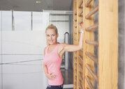 Woman stretching on wall bar in gym - CUF21397