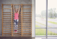 Woman stretching on wall bar in gym - CUF21400