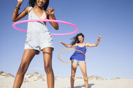 Women on beach using hula hoops - CUF21473