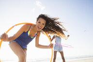 Woman holding hula hoop looking at camera smiling - CUF21479