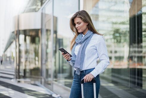 Young businesswoman with suitcase looking at smartphone - DIGF04558