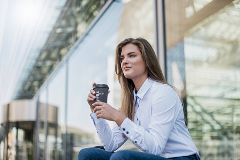 Portrait of young businesswoman with coffee to go - DIGF04564
