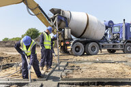Apprentice builders laying concrete foundations on building site - CUF21826