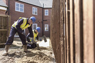 Apprentice builders laying paving stones on building site - CUF21832