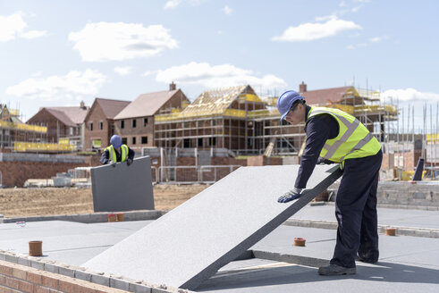 Builders laying insulation on housing building site - CUF21856