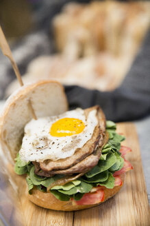 Stacked burger with fried egg at cooperative food market stall - CUF21931