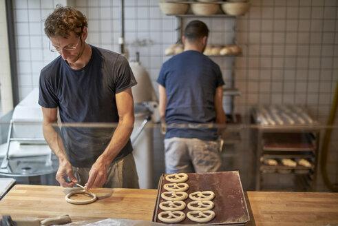 Bakers in bakery preparing fresh pretzls - BEF00116