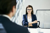Portrait of confident businesswoman with businessman in modern office - BSZF00460
