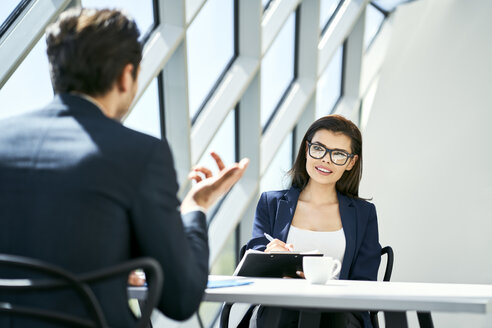 Businesswoman and businessman talking at desk in modern office - BSZF00463