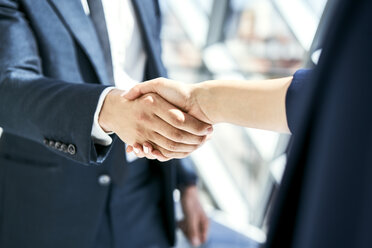 Close-up of handshake of businesswoman and businessman - BSZF00466