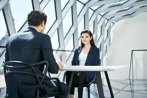 Businesswoman looking at businessman at desk in modern office - BSZF00469