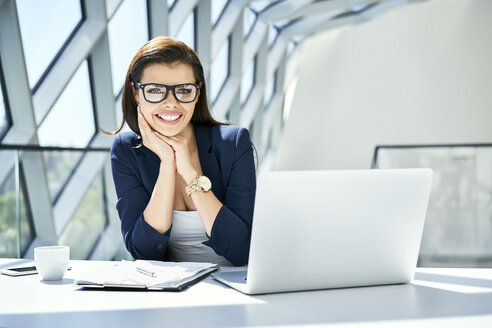 Portrait of smiling businesswoman sitting at desk in modern office - BSZF00472