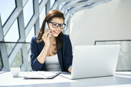 Smiling businesswoman working at desk in modern office - BSZF00475