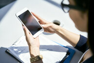 Close-up of businesswoman using cell phone at desk in office - BSZF00478