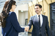 Smiling businessman and businesswoman shaking hands in office - BSZF00493